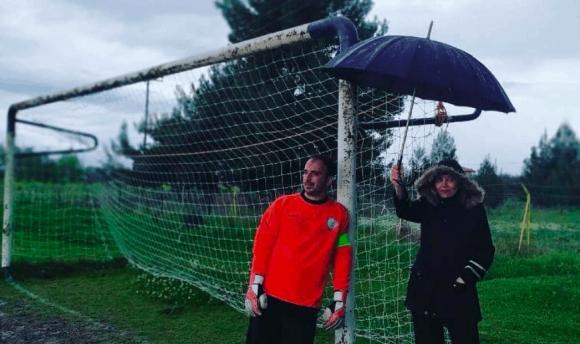Култова сцена! Майка орлица пази футболист от дъжда с чадър в ръка